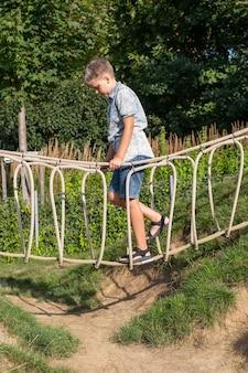 Menino loiro alegre caminha sobre uma ponte de corda em um parque infantil de madeira em um parque público.