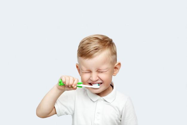 Menino loiro aprendendo a escovar os dentes no banho doméstico
