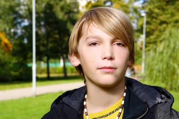 Menino loiro atraente posando no parque