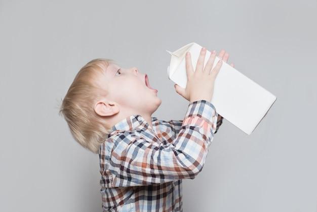 Menino loiro bebe de um grande pacote branco.
