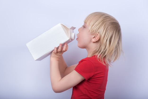 Menino loiro, bebendo leite ou suco de uma caixa grande. retrato de criança com caixa de leite em fundo branco
