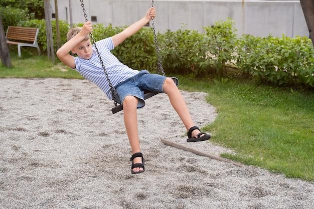 Menino loiro bonito balançando em um balanço do parque público. criança brincar ao ar livre num dia quente de verão ensolarado.