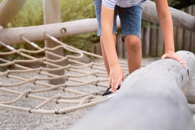 Menino loiro bonito escalando em um playground de madeira em um parque de corda. criança brincar ao ar livre num dia quente de verão ensolarado.