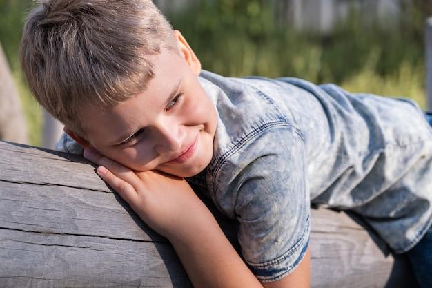 Menino loiro bonito, o menino encontra-se em uma viga de madeira no playground em um parque público.