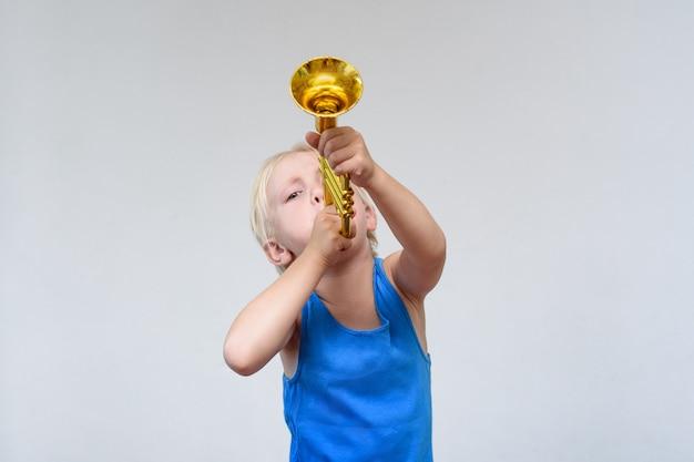 Menino loiro bonito tocando trompete de brinquedo