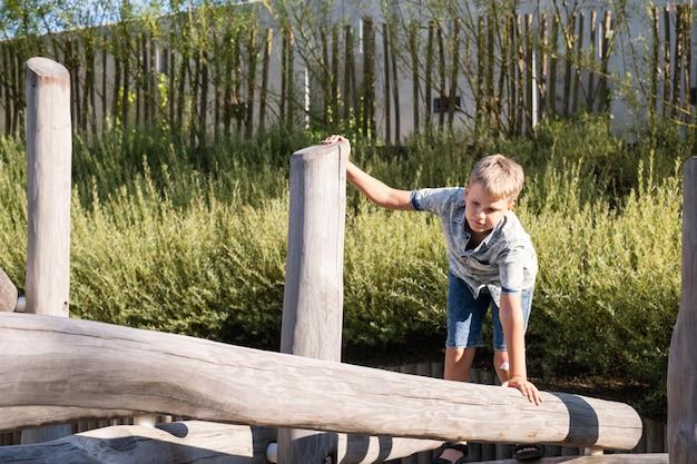 Menino loiro caminha sobre uma viga de madeira em um parque infantil em um parque público.