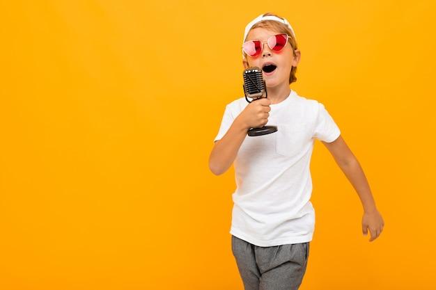 Menino loiro canta em um microfone em uma parede laranja
