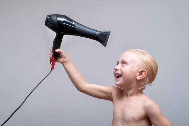 Menino loiro com cabelo molhado é engraçado secado por um secador de cabelo.