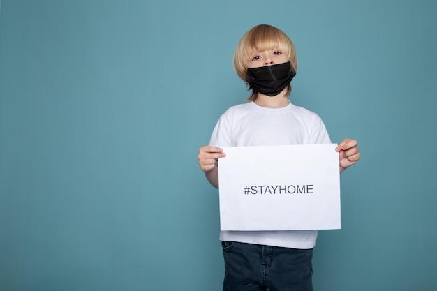 Menino loiro com máscara protetora preta segurando a hashtag em casa contra o coronavírus na parede azul