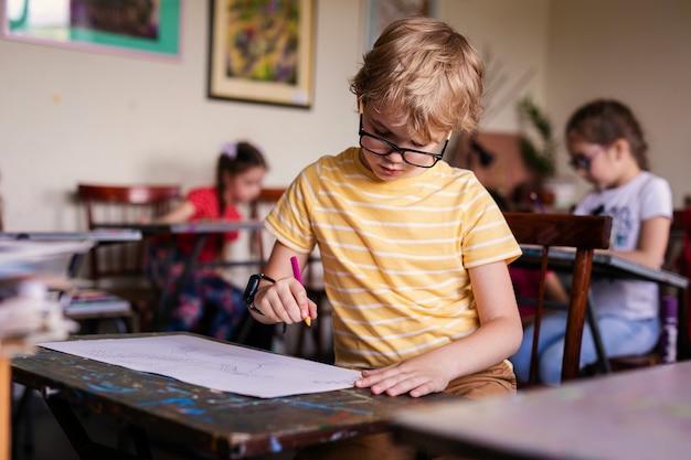Menino loiro com óculos de desenho. grupo de alunos do ensino fundamental em sala de aula na aula de arte