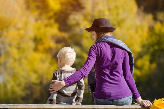 Menino loiro com sua mãe no chapéu, sentado no banco. floresta de outono. vista traseira