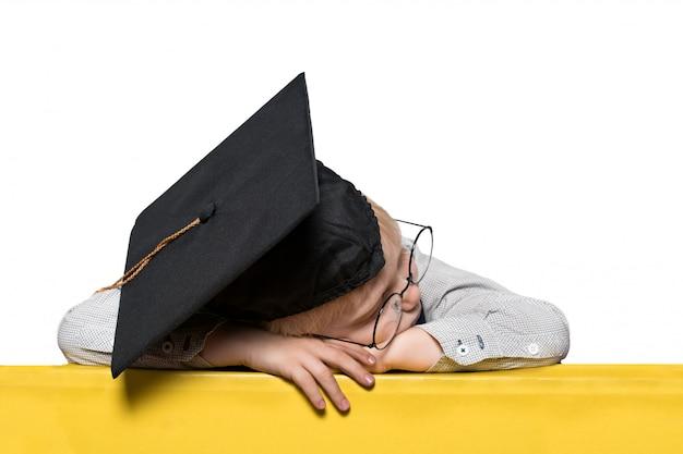 Menino loiro com um chapéu acadêmico e óculos dormindo em cima da mesa.
