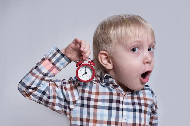Menino loiro com um despertador vermelho nas mãos. rosto surpreso. conceito de manhã