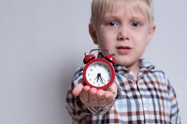 Menino loiro com um despertador vermelho nas mãos.