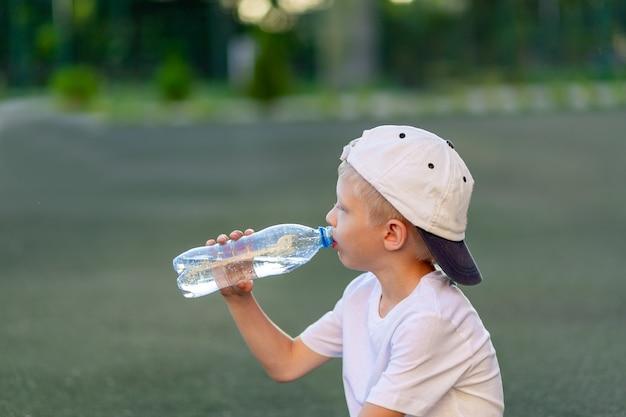 Menino loiro com um uniforme esportivo sentado em um campo de futebol e bebendo água de uma garrafa