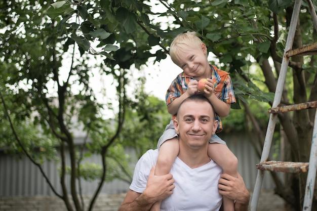 Menino loiro com uma maçã nas mãos nos ombros do pai.