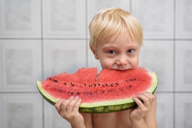 Menino loiro comendo uma fatia de melancia