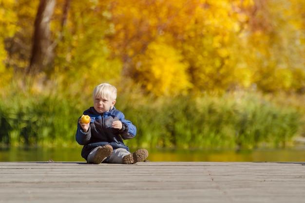 Menino loiro comendo uma maçã no banco dos réus