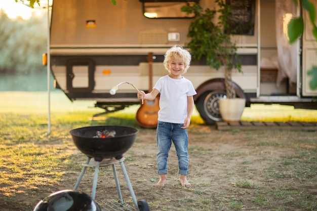 Menino loiro cozinhar marshmallow no acampamento da família