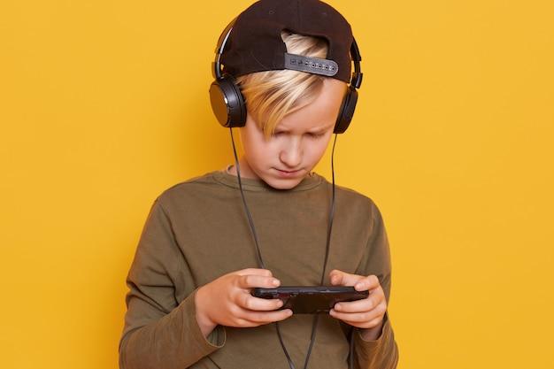 Menino loiro criança jogando jogos móveis no smartphone e usando a internet sem fio enquanto ouve música através de fones de ouvido