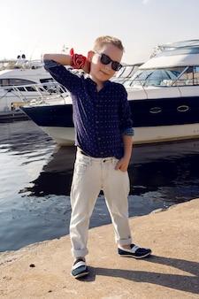 Menino loiro de 8 anos em uma camisa azul, calças leves e óculos de sol caminhando no calçadão à beira-mar com iates atracados perto da costa no verão em clima de sol