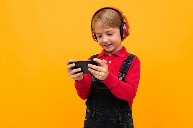 Menino loiro de camisa vermelha com fones de ouvido e um telefone nas mãos assistindo a um vídeo em uma parede amarela