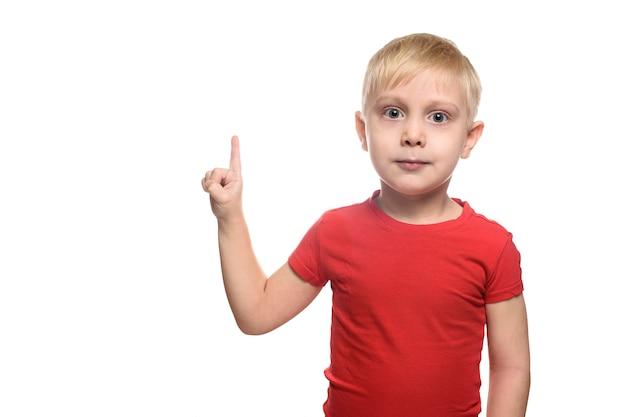 Menino loiro de camiseta vermelha está de pé e apontando com o dedo indicador para cima. isolar em branco