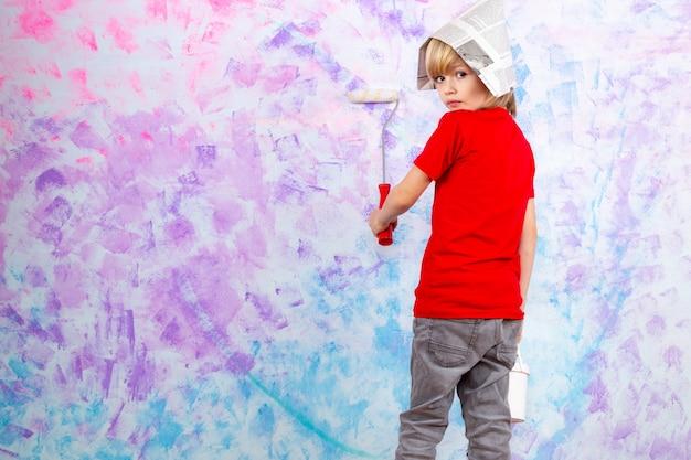 Menino loiro de camiseta vermelha segurando paredes de pintura pincel