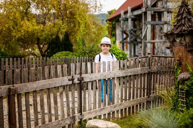 Menino loiro de chapéu e óculos grandes perto da cerca de madeira velha no país
