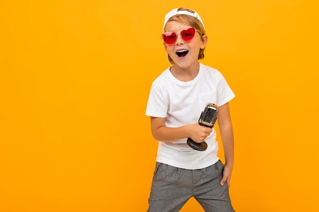 Menino loiro de óculos canta em um microfone em um fundo amarelo