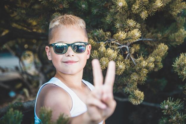 Menino loiro de óculos escuros mostra dois dedos.