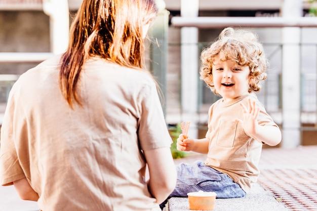 Menino loiro de três anos com lindos cachos feliz com sua mãe depois de tomar sorvete no verão na rua. planos conceituais com crianças no verão nas férias