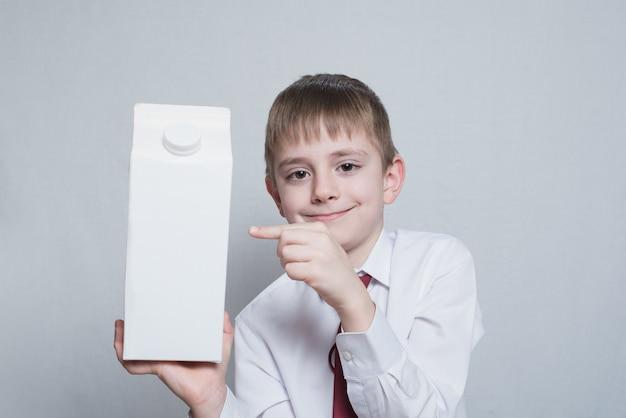 Menino loiro detém e mostra o dedo indicador em uma grande embalagem branca.