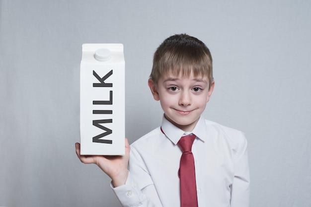 Menino loiro detém e mostra um grande pacote de leite caixa branca. camisa branca e gravata vermelha. luz de fundo