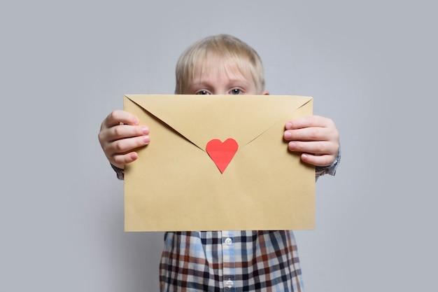 Menino loiro detém um envelope com coração