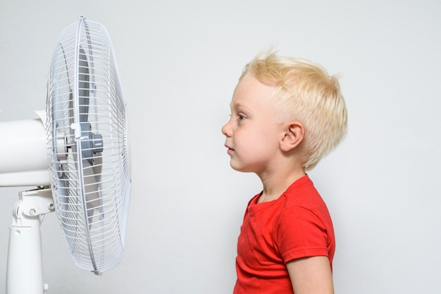 Menino loiro e bonito na camisa vermelha fica perto de um ventilador.