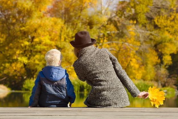 Menino loiro e sua mãe sentada na doca