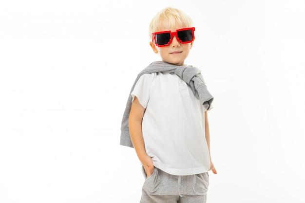 Menino loiro elegante em óculos legais e uma camiseta branca sobre um fundo branco