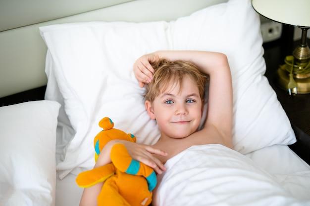 Menino loiro em amarelo t-curto e com raposa de brinquedo laranja na cama branca