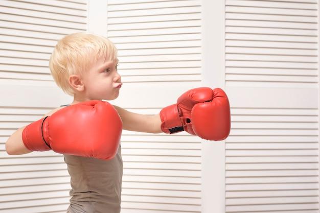 Menino loiro em luvas de boxe vermelhas.