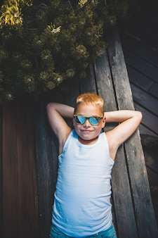Menino loiro em óculos de sol encontra-se no banco.