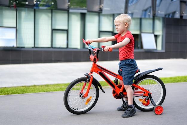 Menino loiro em uma bicicleta infantil. urbano