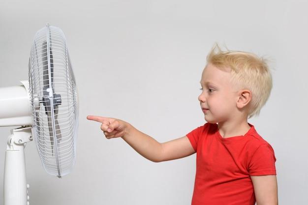 Menino loiro em uma camiseta vermelha toca o ventilador com o dedo.