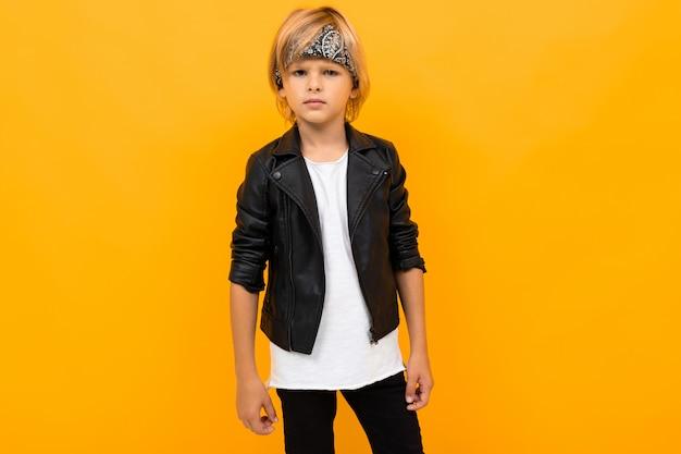 Menino loiro em uma jaqueta de couro preta e uma camiseta branca em laranja