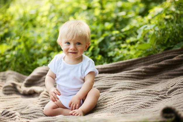 Menino loiro encantador se diverte sentado sobre a manta em um parque de verão