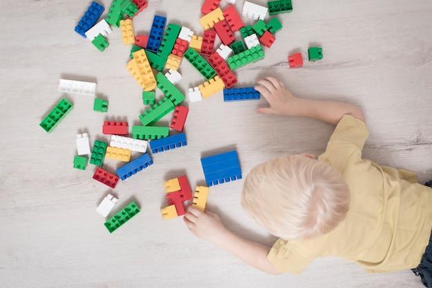 Menino loiro encontra-se no chão entre o construtor. vista do topo