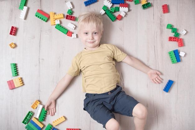 Menino loiro encontra-se no chão entre o designer. vista do topo