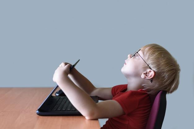 Menino loiro engraçado em copos descansando em um laptop. internet e pré-escolar
