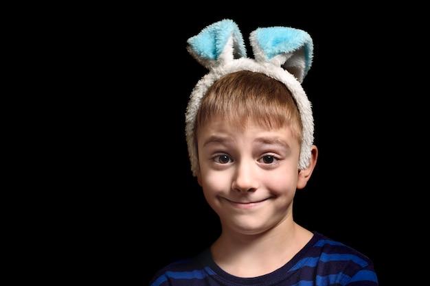 Menino loiro engraçado nas orelhas da orelha contra um fundo preto. retrato de close-up.