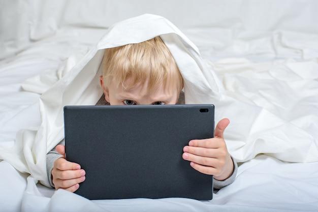 Menino loiro enterrou o nariz no tablet. deitado na cama e escondido debaixo das cobertas. gadget leisure